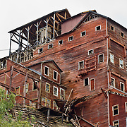 "14-story tall Kennecott Concentration Mill processed copper ore 1911-1938. Kennecott Mines National Historic Landmark and nearby McCarthy nestle under the Wrangell Mountains within Wrangell-St. Elias National Park and Preserve, Alaska, USA. Old mine buildings, artifacts, and colorful history attract summer visitors. Remote McCarthy is connected to Chitina via the McCarthy Road spur of the Edgerton Highway. At the east end of McCarthy Road, visitors must park their vehicle and walk across the footbridge to McCarthy. From McCarthy, a privately-operated shuttle takes visitors 5 miles to Kennecott. After copper was discovered between the Kennicott Glacier and McCarthy Creek in 1900, the Kennecott town, mines, and Kennecott Mining Company were created and named after the adjacent glacier. Kennicott Glacier and River had previously been named after Robert Kennicott, a naturalist who explored in Alaska in the mid-1800s. The corporation and town stuck with a mistaken spelling of ""Kennecott"" with an e (instead of ""Kennicott"" with an i). Partly because alcoholic beverages and prostitution were forbidden in the company town of Kennecott, the neighboring town of McCarthy grew quickly to provide a bar, brothel, gymnasium, hospital, and school. The Copper River and Northwestern Railway reached McCarthy in 1911 to haul over 200 million dollars worth of ore 196 miles to the port of Cordova on Prince William Sound. By 1938, the worlds richest concentration of copper ore was mostly gone, the town was mostly abandoned, and railroad service ended. Not until the 1970s did the area began to draw young people for adventure and the big money of the Trans Alaska Pipeline project. Declaration of Wrangell-St. Elias National Park in 1980 drew adventurous tourists who helped revive McCarthy with demand for needed services. Wrangell-St. Elias National Park and Preserve (the largest National Park in the USA) is honored by UNESCO as a World Heritage Site."