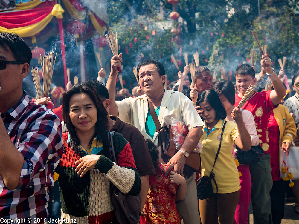 "08 FEBRUARY 2016 - BANGKOK, THAILAND: People hold incense over their heads while they wait in line to get into Wat Mangon Kamlawat, the largest Mahayana (Chinese) Buddhist temple in Bangkok during the celebration of the Lunar New Year. Chinese New Year is also called Lunar New Year or Tet (in Vietnamese communities). This year is the ""Year of the Monkey."" Thailand has the largest overseas Chinese population in the world; about 14 percent of Thais are of Chinese ancestry and some Chinese holidays, especially Chinese New Year, are widely celebrated in Thailand.       PHOTO BY JACK KURTZ"