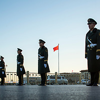 China, Beijing, Setting sun silhouettes military police guards standing in line outside Forbidden City during ceremonial lowering of Chinese flag in Tiananmen Square