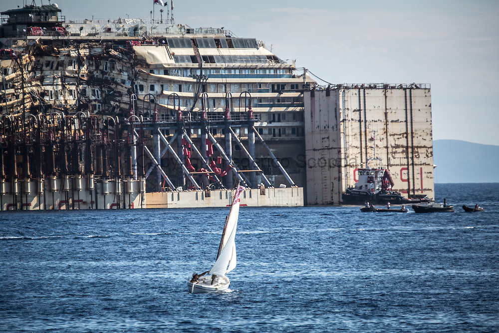 A man with a small sail boat leaves the Giglio port that is closed to traffic to salute the Costa Concordia