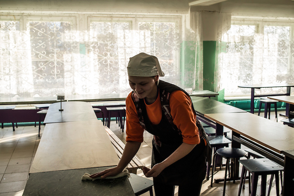 A woman cleans tables in a school cafeteria on Thursday, October 24, 2013 in Baikalsk, Russia.