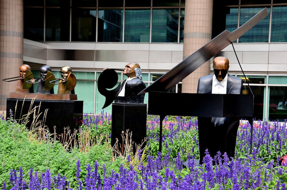 Symphonic Suite Sculpture by Michael Cunningham at North Point Tower in Cleveland, Ohio<br /> In a flower bed outside of the 19 story North Point Tower in downtown Cleveland, Ohio, is a sculpture of an orchestra, including this pianist and horn section. Not shown is the nearby string section. All of the full-size musicians are wearing a tux. This 1990 ensemble by Michael Cunningham is called, &ldquo;Symphonic Suite.&rdquo;