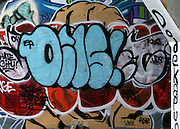 At the entrance to a dark underpass in Urban Atlanta, is a canvas of varied and colorful urban artwork, gang related, grafitti.