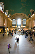 A family points to the ceiling of New York city's Grand Central Station as commuters walk around them.