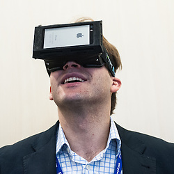 London, UK - 17 March 2014:  a man wears vrAse  augmented reality oculars by Eyedak at the Wearable Technology Conference at Olympia in London.