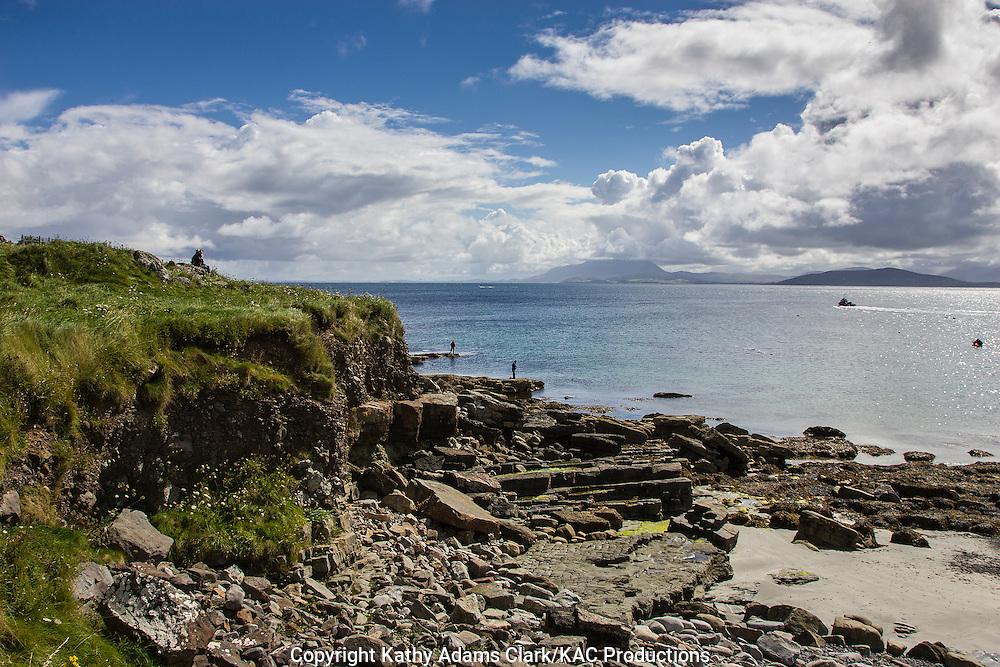 Fishermen on rocky coastline of Clare Island off coast of western Ireland.