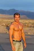 muscular man without a shirt in the desert at sunset