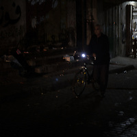 An old man is seeing going back home with his bike, his district is in total darkness. Un anziano torna a casa durante la sera, il proprio quartiere e' completamente al buio.