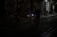 An old man is seeing going back home with his bike, his district is in total darkness. Un anziano torna a casa durante la sera, il proprio quartiere e' completamente al buio.