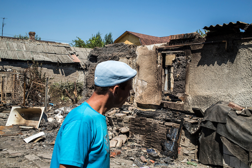 A man surveys the damage from a shell which hit and burned a house in the Oktyabrskaya neighborhood on Sunday, July 27, 2014 in Donetsk, Ukraine.
