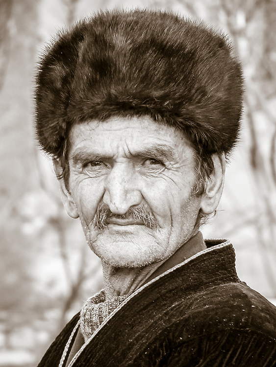 Portrait of an old Tajik man wearing a Russian fur hat and posing with an inquisitive look