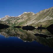 Early morning at Lake Sabrina in the Sierra Nevada Mountains.  The islands in the lake are just silhouettes.  Lake Sabrina is off of Hwy 168, west of Bishop, California.  The lake is a popular desination for fishing and hiking.