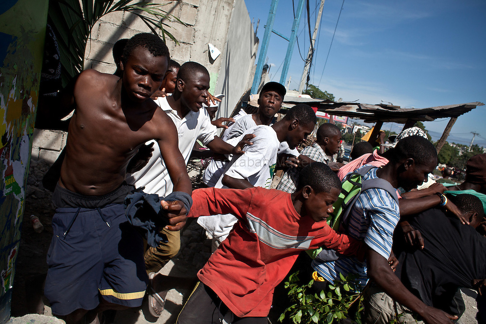 The presidential election in Haiti takes a bad way with fraud suspicions and troubles from some supporters in polling stations./// Martelly's supporters flee the police during a demonstration, 28 november 2010 in the streets of Port-au-Prince, to protest against the fraud during the vote for presidential election and ask for the cancellation of the poll.