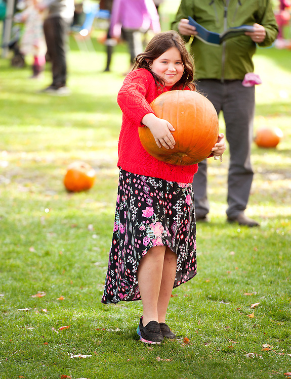 Nine year old Vanessa Sternberg carries a large pumpkin at the Pumpkin Patch at Stan Clarke Park.