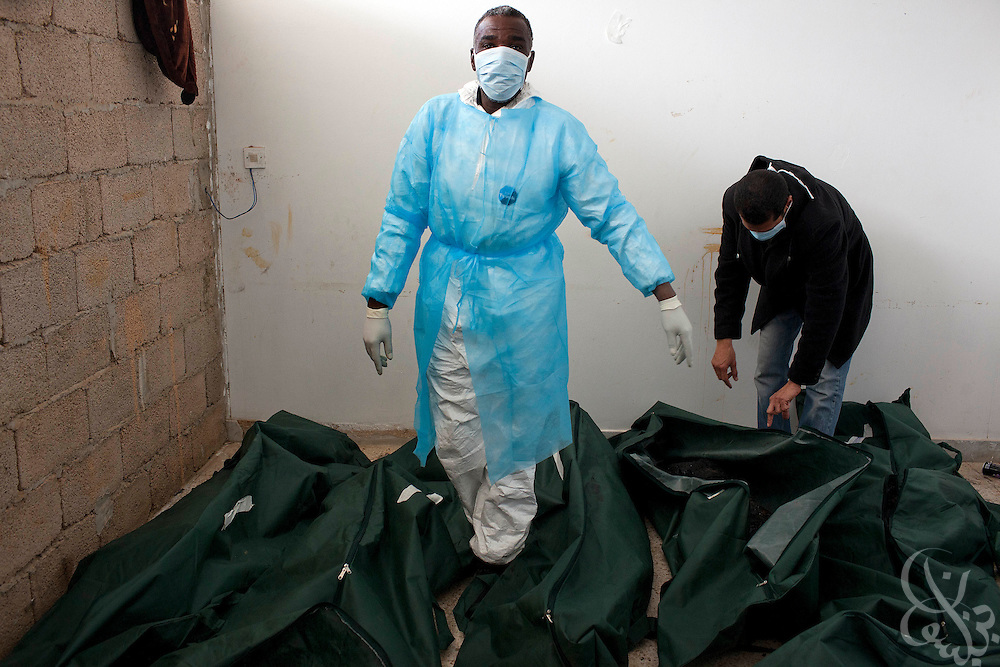 Morgue workers examine the remains of what are believed to be executed and burned military officers February 24, 2011 at the al Jala'a hospital in Benghazi, Libya. Local officials say that the officers were killed after they refused to follow Qaddafi's orders to shoot civilians during the uprising in Benghazi, although this has not been independently confirmed. .Slug: Libya.Credit: Scott Nelson for the New York Times