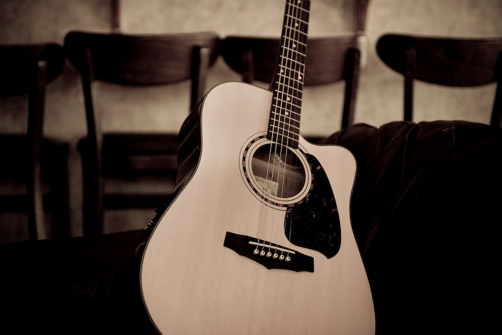 Acoustic guitar leaning against couch with stools behind. Image in sepia tone.
