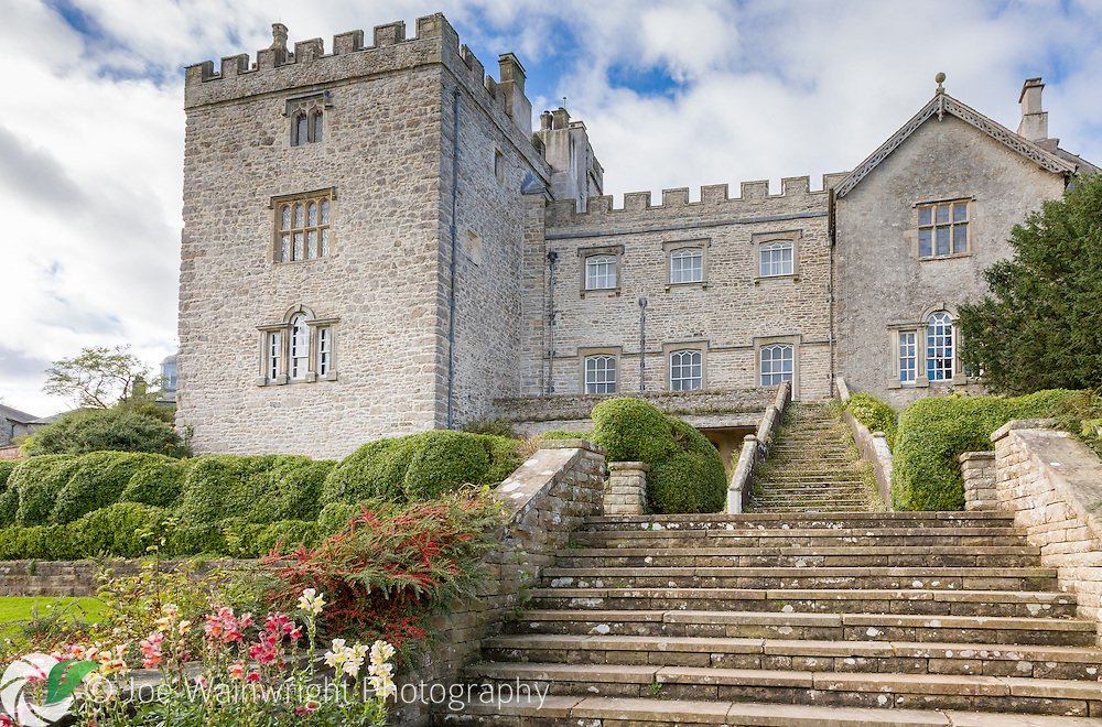 Overhung with cotoneaster, box and ivy, steps rise from the garden to the medieval Sizergh Castle, Cumbria.