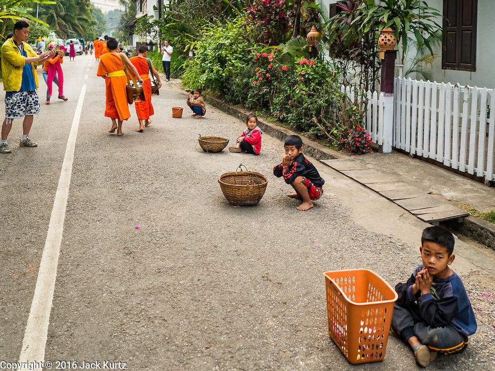 "11 MARCH 2016 - LUANG PRABANG, LAOS: A tourist photographs Buddhist monks during the tak bat while Lao children wait for more monks to pass them. The monks give the children food items they don't use, like candy, that people give to the monks. Luang Prabang was named a UNESCO World Heritage Site in 1995. The move saved the city's colonial architecture but the explosion of mass tourism has taken a toll on the city's soul. According to one recent study, a small plot of land that sold for $8,000 three years ago now goes for $120,000. Many longtime residents are selling their homes and moving to small developments around the city. The old homes are then converted to guesthouses, restaurants and spas. The city is famous for the morning ""tak bat,"" or monks' morning alms rounds. Every morning hundreds of Buddhist monks come out before dawn and walk in a silent procession through the city accepting alms from residents. Now, most of the people presenting alms to the monks are tourists, since so many Lao people have moved outside of the city center. About 50,000 people are thought to live in the Luang Prabang area, the city received more than 530,000 tourists in 2014.       PHOTO BY JACK KURTZ"