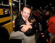 PRICE CHAMBERS / NEWS&GUIDE.Jackson Hole High School swim team sophmore Juliane Kallas, left, hugs senior Becky Griest after they exit the bus returning from the state meet in Gillette. The team brought home a state title for the second year running, breaking two state records on their way to first place with a team score of 318.