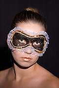young teenage female model with a black make up mask around her eyes on black background model released studio shot