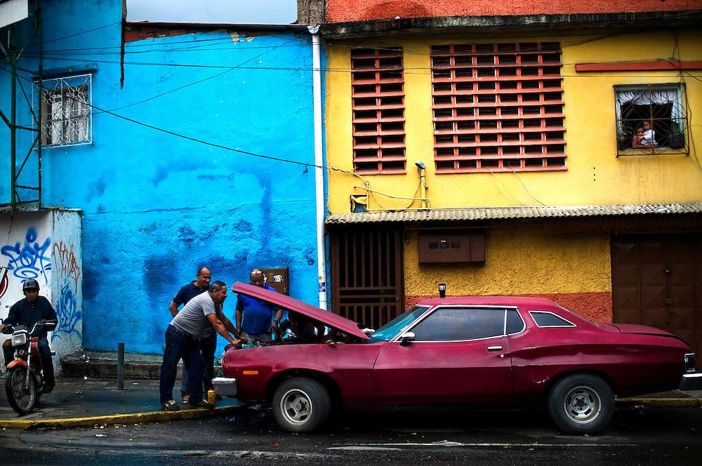 Humberto Melo, 57, (gray shirt), repairs a 1974 Ford Fairlane with Freddy Gomez, 54, (blue shirt) and Rigoberto Melo, 52, in Caracas, Venezuela.