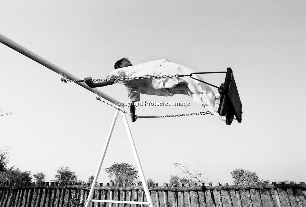 Ueberschwenglich schaukelt WUD, 8 Jahre alter Junge, auf der Kinderschaukel. Provinz Lop Buri, Thailand.WUD, boy age 8, swinging joyful at the playground..Province Lop Buri, Thailand......