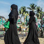 Two young muslim women walk out from the beach of Cox's Bazar, Bangladesh. In the background, the typical bengali rickshaws, the most common way of transport here