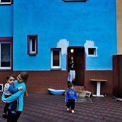 "Veronika Sindelárová watches her children Fabián Gina, 1, and Rinaldo Gina, 2, play with her half-sister outside their home in Ostrava, Czech Republic on March 1, 2012. Veronika was one of 18 Roma children who were represented in the D.H. and Others v. Czech Republic case, the first challenge to systemic racial segregation in education to reach the European Court of Human Rights. When this case was first brought in 2000, Roma children in the Czech Republic were 27 times more likely to be placed in ""special schools,"" intended for the mentally disabled, than non-Roma children. In 2007, the Grand Chamber of the European Court of Human Rights ruled that this pattern of segregation violated nondiscrimination protections in the European Convention on Human Rights. Despite this landmark decision, little change has occurred: the ""special schools"" have been renamed but follow the same substandard curriculum and Roma continue to be assigned to these schools in disproportionate numbers. The process of integration has barely begun."