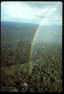 Rubber tappers huts sit at end of rainbow as it arcs across sky over vast jungle; Amazonas state Brazil