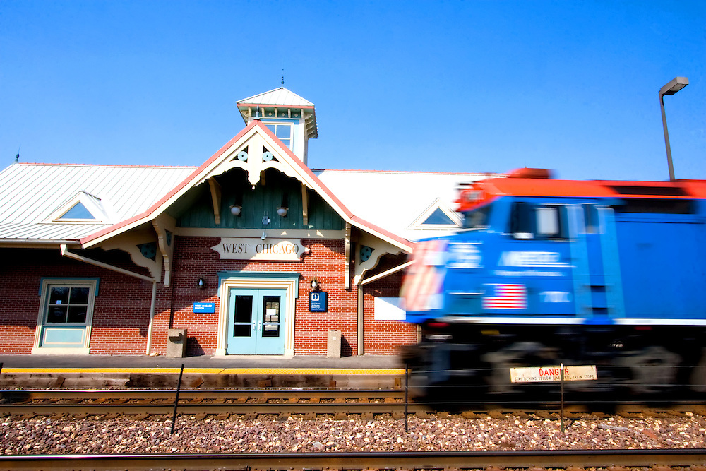 The ornate depot at West Chicago, IL, looking almost like something from Disney World, stands next to the tracks as a westbound Metra train pulls in.