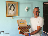 Havanna Vieja, old city, man selling faked cigars, portrait of a young girl on the wall, Cuba, Havanna