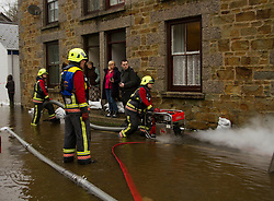 © Licensed to London News Pictures. 22/12/2012. Helston, UK. Fire crew pump water from around properties in Helston after the River Cober burst its banks over night after heavy rain across the South West. The Environment Agency issued a Severe flood warning for the River Cober. Photo credit : Ashley Hugo/LNP