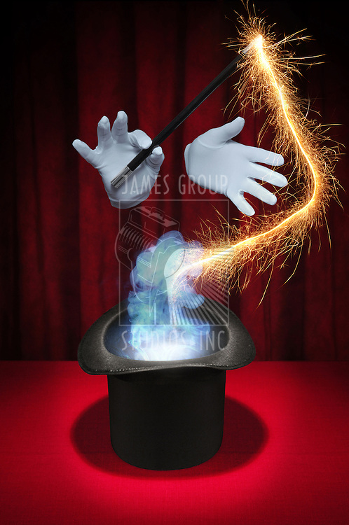 White gloved hands holding a magic wand above a magician's top hat producing sparks and smoke on a red background