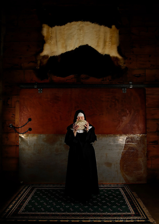 """BETHLEHEM, CT- 15 DECEMBER 2005- Mother Noella Marcellino of the Abbey of Regina Laudis  sniffs a Bethlehem Cheese while having her portrait taken at the abbey. Mother Noella has won international acclaim for her cheese making. She received a doctorate in microbiology from the University of Connecticut and also was awarded a Fulbright scholarship to go to France to study native fungus strains. She is the subject of a documentary film entitled """"The Cheese Nun"""".    (Photo by Robert Falcetti)"""