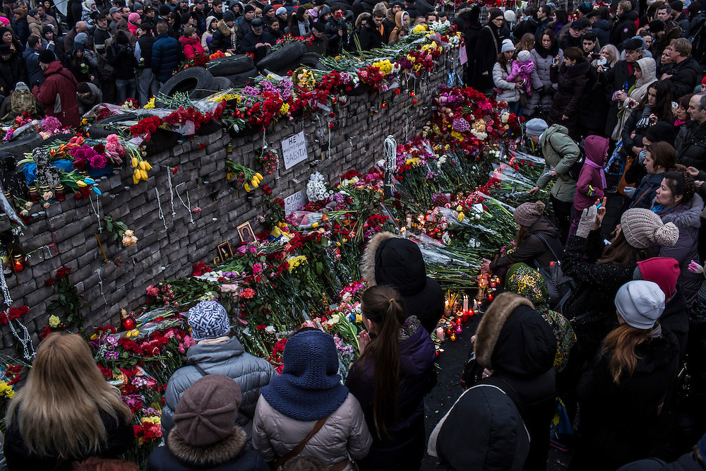 KIEV, UKRAINE - FEBRUARY 23: People lay flowers and pay their respects at a memorial for anti-government protesters killed in clashes with police in Independence Square on February 23, 2014 in Kiev, Ukraine. After a chaotic and violent week, Viktor Yanukovych has been ousted as President as the Ukrainian parliament moves forward with scheduling new elections and establishing a caretaker government. (Photo by Brendan Hoffman/Getty Images) *** Local Caption ***