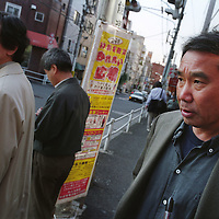 Haruki Murakami (on right), born 1949,  Japanese contemporary fiction author / novelist / essayist. Photographed in Kagurazaka district of Tokyo, Japan. 14.12.2004 Murakami is author of noted books such as 'The Elephant Vanishes', 'Norwegian Wood', 'A Wild Sheep Chase', 'Underground', 'After the quake' and 'Kafka on the Shore'.