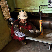 Workers operating an iron plates bending machine