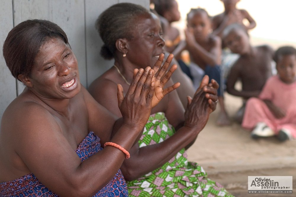 """Women chanting during a """"coming out"""" ceremony at a fetish shrine in Aflao, Volta Region, Eastern Ghana. A woman was released after spending three months in a small, dark room, hoping that she'd then be able to find a husband. Despite most Ghanaians being adamant followers of christianism or islam, many of them still maintain traditional beliefs. When facing a problem of any nature, some people will visit a local fetish shrine, looking for help. The main priest will consult the oracles and tell the person in need what has to be done for the problem to go away. People will typically be asked to """"serve"""" the shrine for weeks, sometimes months, as their families pay the priest for their upkeep."""