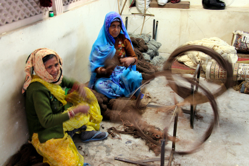 Asia, India, Jaipur. Indian women spinning wool for use in making carpets.