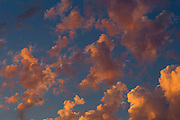 """A series of cumulus clouds develop and grow as the sun sets over Snohomish County, Washington. Cumulus means """"heap"""" or """"pile"""" in Latin, and the clouds typically form where warm air rises and reaches a level of cold air where the moisure in the air condenses."""