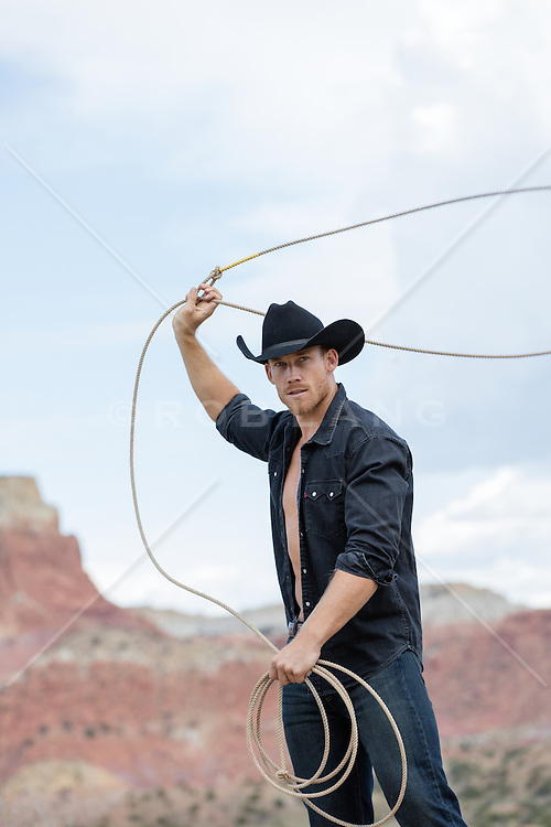 sexy cowboy with an open shirt using a lasso on a ranch