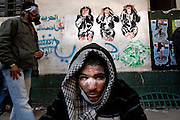 An Egyptian protester recovers from a tear gas attack in front of revolutionary graffiti during clashes with security forces November 22, 2011 near Tahrir square in central Cairo, Egypt. Thousands of protestors demanding the military cede power to a civilian government authority clashed with Egyptian security forces for a fourth straight day in Cairo, with hundreds injured and at least 29 protestors killed so far.  (Photo by Scott Nelson)