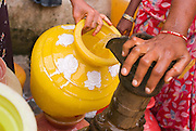 Ladies pumping water. Santhome Beach and adjoining Marina Beach in Chennai, India were hit hard by the 2004 Tsunami. Fishermen and their families were the main victims living in their lightweight huts on the long and flat beaches of the area. All structures within 300 metres of the sea have now been banned and any left standing after the Tsunami were demolished. The fishermen and their families have now been relocated to government blocks of flats which has become a Santhome slum for fishermen and their families.