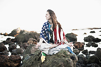 Beautiful woman draped in the american flag and tibetan prayer flags.