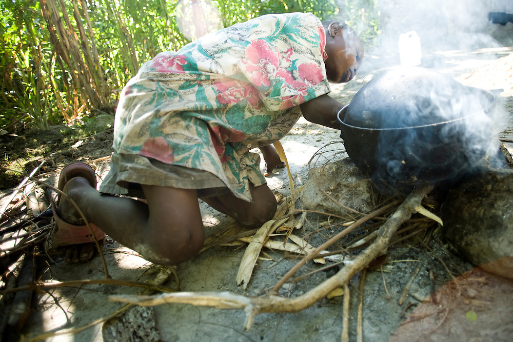 A boy cooks rice with wood.