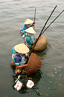 Vietnamese women in conical hats fishing the cold waters of Tay Ho Lake, Hanoi.