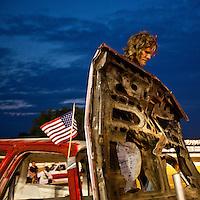 USA, Maryland, Mechanicsville, Man stands over hood of damaged truck after participating in Demolition Derby at Potomac Speedway