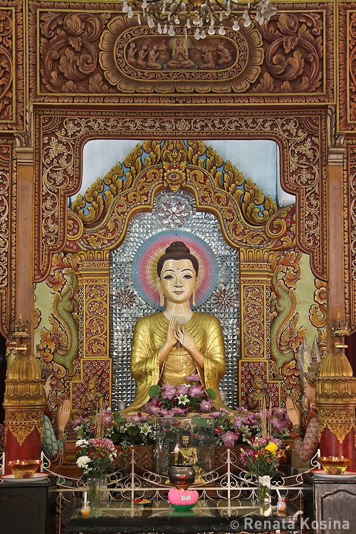 Painted woodcarvings and the statue of Buddha inside the Dhammikarama Burmese Buddhist Temple on Penang, Malaysia.
