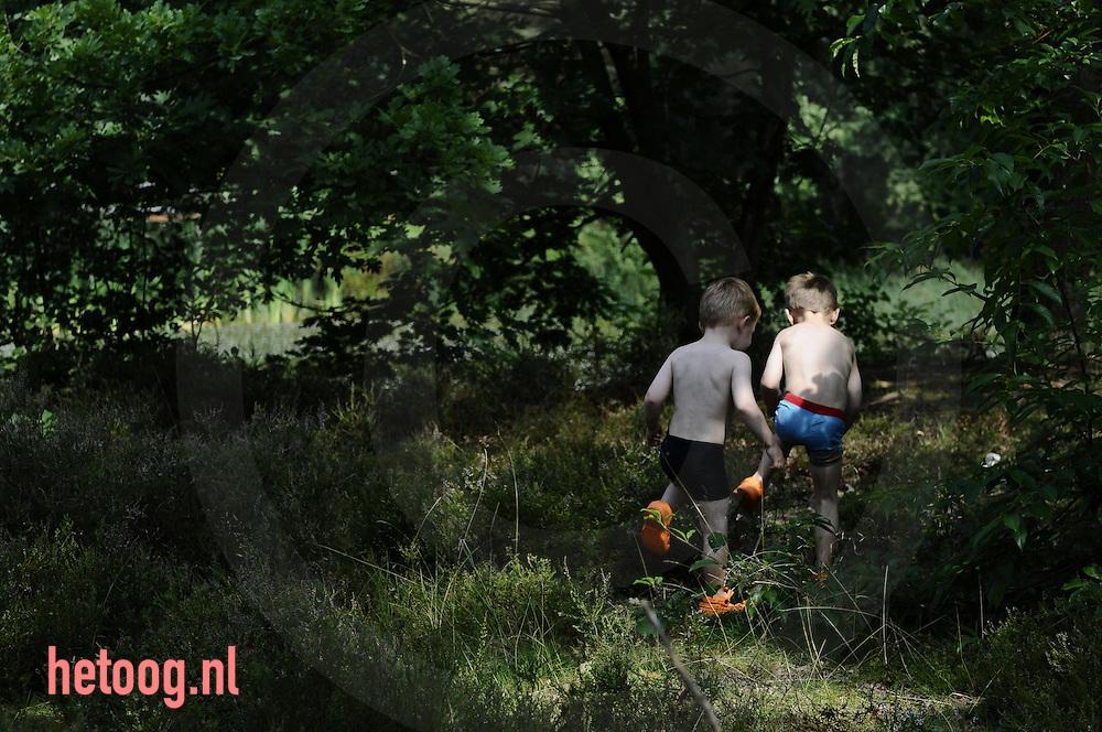 een peuter en een kleuter spelen op vakantie in het bos.
