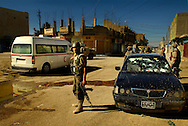 After shooting a fleeing insurgent's vehicle, members of the Iraqi army, 4th Battalion, 2nd Brigade, 5th Division, provide medical assistance to the car's occupants during an operation in Old Baqubah, Iraq, on March 11, 2007.